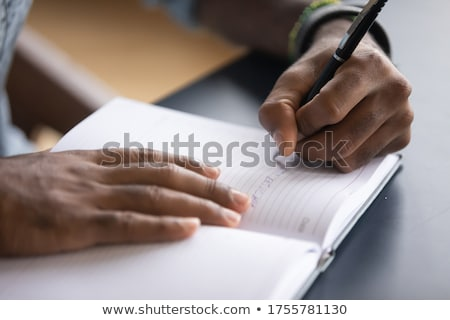 Stock photo: Man writing in a personal organizer