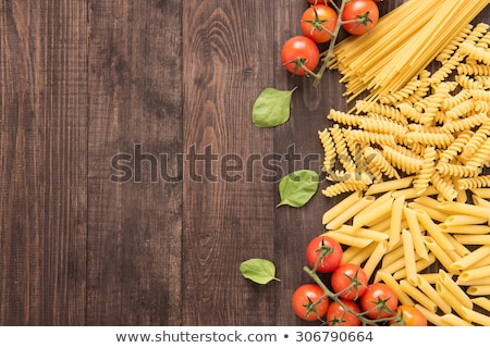 Raw pasta on wooden background Stock photo © elly_l