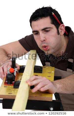 Tradesman blowing shavings off of a wooden plank Stock photo © photography33