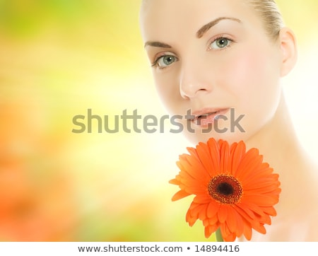 beautiful young woman with gerbera flower over abstract blurred stock photo © nejron