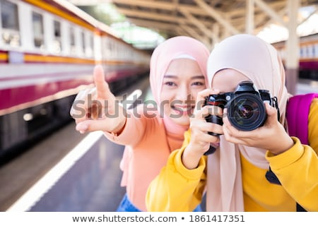 Pretty young woman with a DSLR camera outdoors, using a tripod,  Stock photo © lightpoet