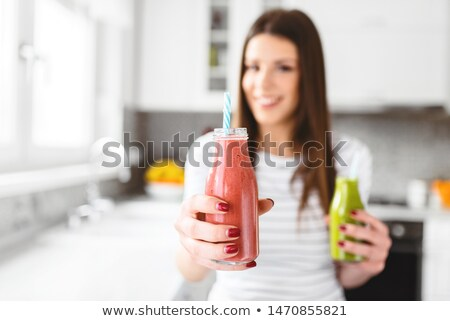 smiling woman holding bottle of milk with straw and looking to camera on white Stock photo © LightFieldStudios