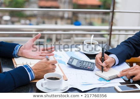 Cropped image of business man sitting by table in cafe Stock photo © deandrobot