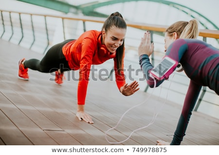 Attractive woman exercising with a personal trainer outside at s Stock photo © boggy