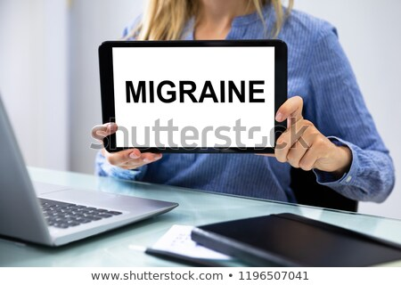 Businesswoman Showing Migraine Word On Digital Tablet Stock photo © AndreyPopov
