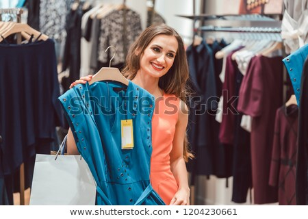 Woman pondering buying a blue dress in fashion store Stock photo © Kzenon