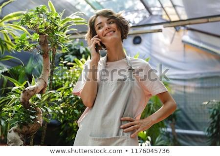 Woman gardener standing over plants in greenhouse talking by mobile phone. stock photo © deandrobot