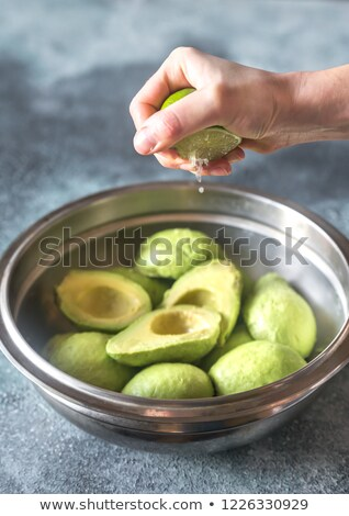 Hand squeezing lime on halved avocados Stock photo © Alex9500
