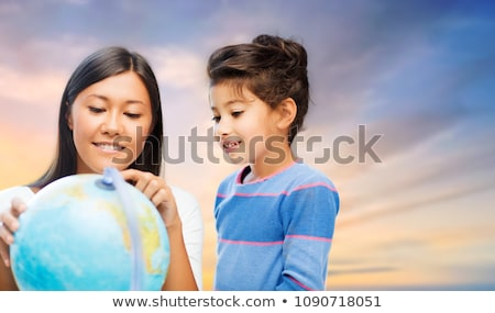 happy mother and daughter with globe over sky Stock photo © dolgachov