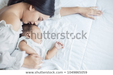 close up of asian mother holding sleeping baby boy stock photo © dolgachov