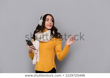Portrait of beautiful woman wearing ear muffs and scarf using mo Stock photo © deandrobot