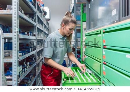 Woman in storeroom of key maker store Stock photo © Kzenon