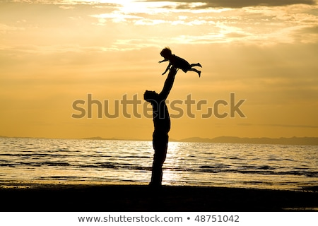 Father Throwing His Young Daughter In The Air At Beach Stock photo © AndreyPopov