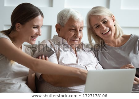 Stockfoto: Contemporary Mobile Seniors Sitting On Couch