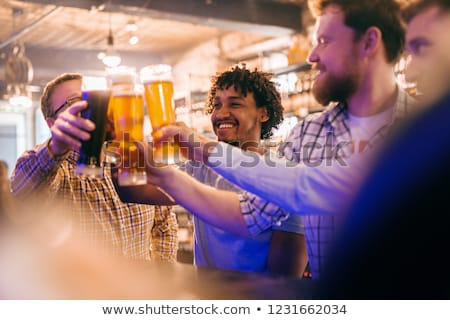 Young multicultural friends with beer while cheering for their hockey team Stock photo © pressmaster