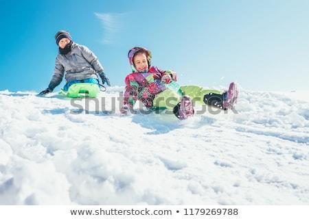 happy boy sliding on sled down snow hill in winter Stock photo © dolgachov
