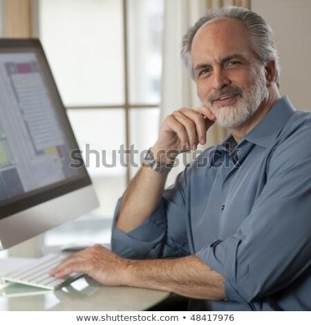 Businessman Looking At Camera Sitting Near Computer Monitor Stockfoto © EdBockStock