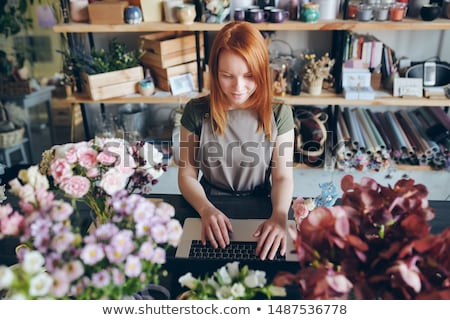Pretty florist working with social media of flower shop Stock photo © pressmaster