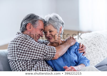 Side view of happy senior couple head to head and embracing each other on beach in the sunshine Stock photo © wavebreak_media