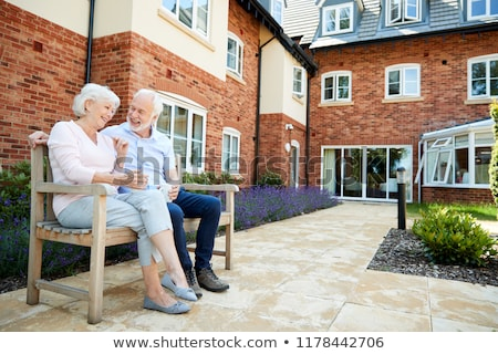 side view of senior couple relaxing on bench in garden on a sunny day stock photo © wavebreak_media