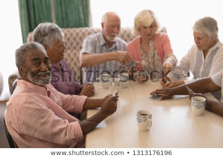 Stock photo: Front view of group of senior people playing cards in living room at home
