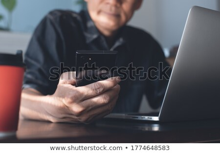 Stock photo: Front View Of Asian Businessman Using Mobile Phone And Laptop In The Modern Office
