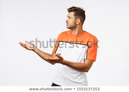 Disappointed sad bearded masculine male trainer in sports t-shirt, looking upset left raising hands  Stock photo © benzoix
