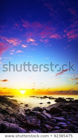 Stock photo: Rocky seacoast at dusk. Long exposure vertical shot.