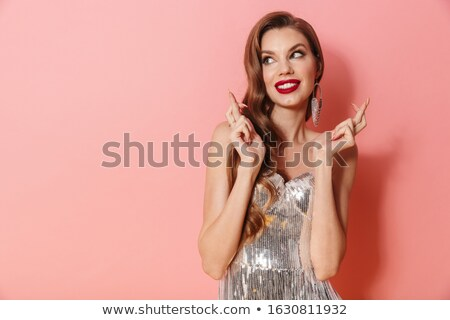 Woman in bright sequins dress make fingers crossed gesture. Stock photo © deandrobot