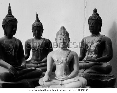 Stock photo: One White Stone Buddha and Three Black statue