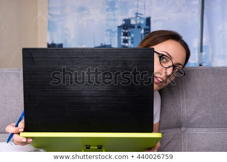 Woman peeking out from behind her laptop Stock photo © photography33