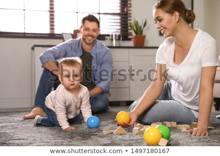 Parents watching their daughter play with blocks Stock photo © photography33