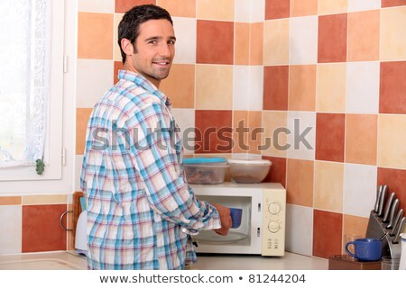 Man putting cup in microwave Stock photo © photography33