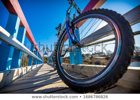 bicycle on wooden fence of bridge at sunset stock photo © xuanhuongho