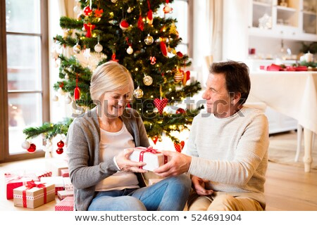 senior couple with gifts in front of christmas tree stock photo © monkey_business
