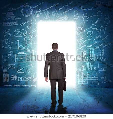 Businessman in suit with briefcase stepping through door Stock photo © cherezoff