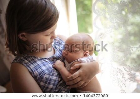 Stock photo: Older sister taking care of her younger sister