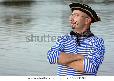 Man with drawed beard and whiskers in pirate suit near pond is looking away stock photo © Paha_L