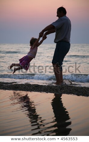 grandfather rotates child on sunset at sea stock photo © paha_l