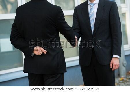 dishonest businessman shaking hands with partner stock photo © andreypopov