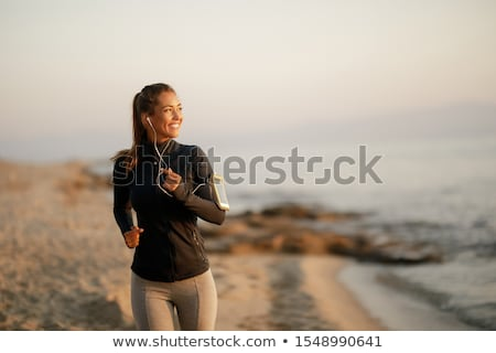 woman with earphones jogging or running Stock photo © dolgachov