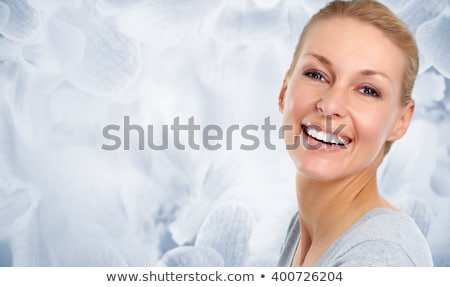 Beautiful woman face over blue abstract background. Stock photo © Kurhan