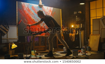 young man painting with roller stock photo © nyul