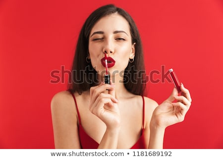 Woman posing isolated holding lip gloss doing makeup. Stock photo © deandrobot