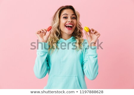 Photo of smiling woman in basic clothing holding two macaron bis Stock photo © deandrobot