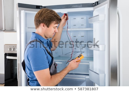 Stock photo: Serviceman In Overall Working On Fridge