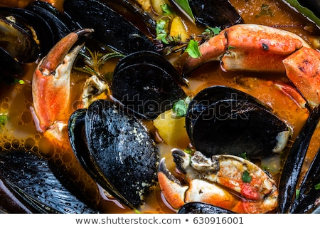 close up of seafood soup with fish and mussels stock photo © dolgachov