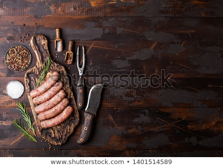Raw beef and pork sausage on old chopping board with vintage knife and fork on wooden background.Sal Stock photo © DenisMArt
