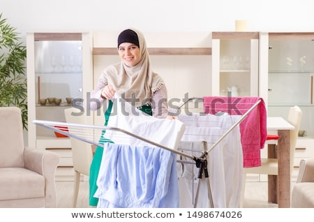 Woman in hijab doing clothing ironing at home Stock photo © Elnur