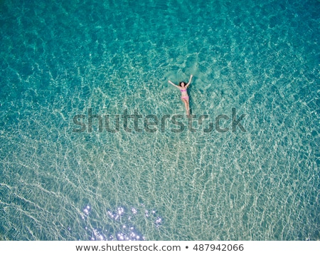 Aerial top view of woman snorkeling from above, girl snorkeler swimming in a clear tropical sea wate Stock photo © galitskaya